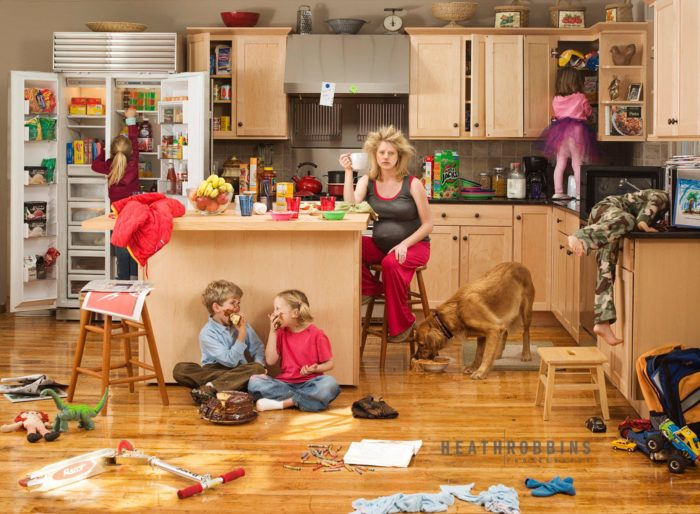 Уставшая беременная женщина сидит на кухне в страшном беспорядке. Мальчик и девочка едят торт на полу, мальчик лезет головой в микроволновку, девочка в шкаф, еще одна девочка в холодильник