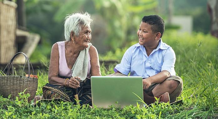 Бабушка смотрит на мальчика, который показывает ей ноутбук.