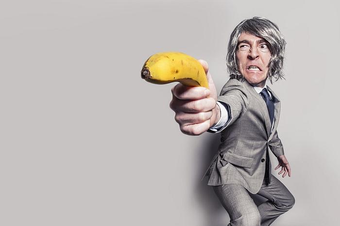 Испуганный мужчина в сером костюме держит банан как пистолет