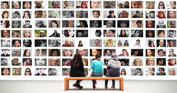 Трое сидят на скамейке и смотрят на стену, обвешанную фотографиями людей из разных стран и культур. Какая-то межкультурная выставка фотографии, по всей видимости