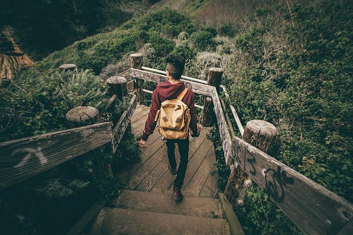 Азиатский юноша спускается по лестнице в парке