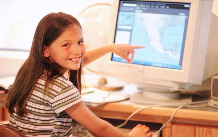 Девочка сидит за компьютером и улыбается, показывает пальцем на карту Центральной Америки