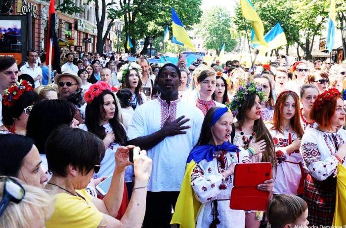 Tłum młodych ludzi w ukraińskich strojach ludowych, w centrum stoi czarnoskóry młody człowiek, patetycznym gestem położył rękę na piersi