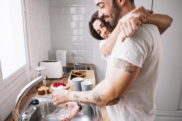 Мужчина моет посуду, его обнимает женщина, оба улыбаются