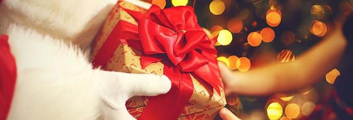 święty Mikołaj przekazuje prezent do rąk dziewczynki na Boże Narodzenie