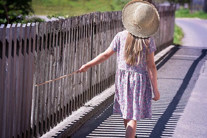 Девочка идет вдоль заборчика и ведет по нему палочкой