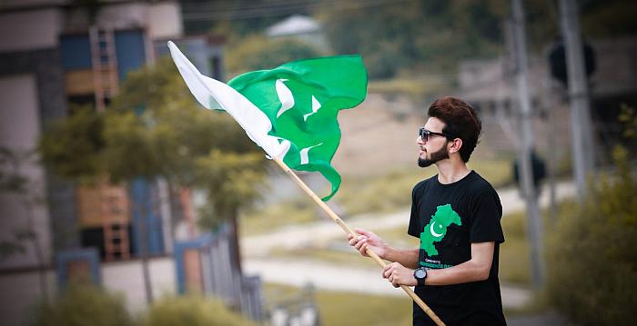 Chłopak w koszulce z flagą Pakistanu wymachuje flagą Pakistanu