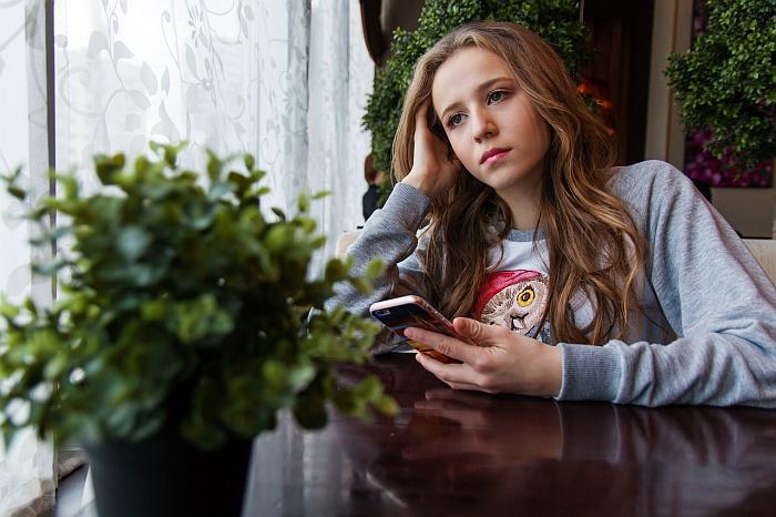 Dziewczyna smutnie siedzi z komórką i czeka, kiedy do niej napisze narzeczony z Pakistanu