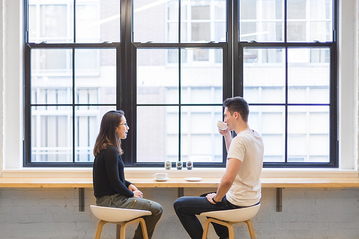 Para mieszana siedzi i rozmawia przy kawie